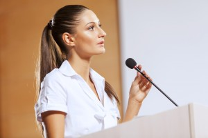 Businesswoman standing on stage and reporting for audience shutterstock_283553633